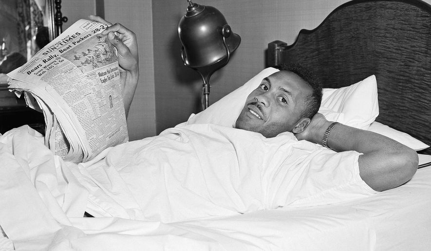 FILE - In this Nov. 8, 1954, file photo, Chicago Cardinals football player Ollie Matson, injured the day before in a football game in Philadelphia, is shown in a hospital bed in Chicago. Ollie Matson was an Olympic sprinter, a Hall of Fame football player and a loving father. His son, Ollie Jr., believes the repeated blows to the head his dad received in the NFL cheated them out of 20 years of good times together. (AP Photo/Charles E. Knoblock, File)