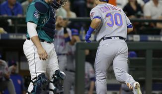 New York Mets' Michael Conforto (30) heads to the dugout past Seattle Mariners catcher Mike Zunino after Conforto hit a solo home run during the eighth inning of a baseball game, Friday, July 28, 2017, in Seattle. Conforto also homered in the third inning. (AP Photo/Ted S. Warren)