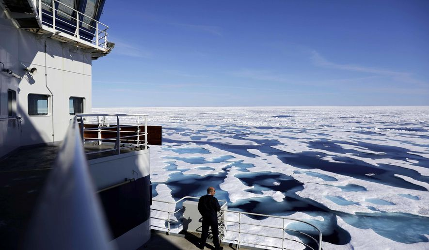 FILE - In this  July 22, 2017 file photo, Canadian Coast Guard Capt. Victor Gronmyr looks out over the ice covering the Victoria Strait as the Finnish icebreaker MSV Nordica traverses the Northwest Passage through the Canadian Arctic Archipelago.  After 24 days at sea and a journey spanning more than 10,000 kilometers (6,214 miles), the Finnish icebreaker MSV Nordica has set a new record for the earliest transit of the fabled Northwest Passage.  The once-forbidding route through the Arctic, linking the Pacific and the Atlantic oceans, has been opening up sooner and for a longer period each summer due to climate change. Sea ice that foiled famous explorers and blocked the passage to all but the hardiest ships has slowly been melting away in one of the most visible effects of man-made global warming. (AP Photo/David Goldman, File)