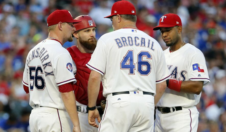 Texas Rangers pitching coach Doug Brocail (46) talks with starting pitcher Austin Bibens-Dirkx (56) and teammates Jonathan Lucroy, rear, and Elvis Andrus, right, during the third inning of the team's baseball game against the Baltimore Orioles on Saturday, July 29, 2017, in Arlington, Texas. (AP Photo/Tony Gutierrez)
