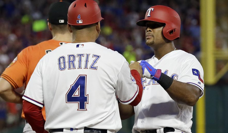 Texas Rangers first base coach Hector Ortiz (4) congratulates Adrian Beltre, right, on his single off Baltimore Orioles' Kevin Gausman during the fourth inning of a baseball game, Saturday, July 29, 2017, in Arlington, Texas. The hit is the 2,999th of Beltre's career. (AP Photo/Tony Gutierrez)