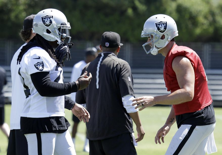 Oakland Raiders running back Marshawn Lynch, left, and quarterback Derek Carr converse during an NFL football training camp on Saturday, July 29, 2017, in Napa, Calif. (AP Photo/Ben Margot)