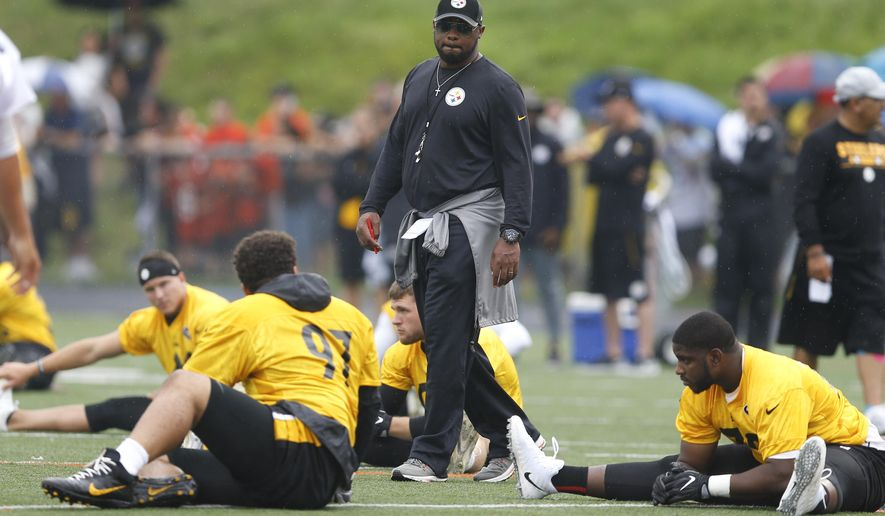 Pittsburgh Steelers coach Mike Tomlin walks between players as they warm up during practice at NFL football training camp at Latrobe High School in Latrobe, Pa., Friday, July 28, 2017. (AP Photo/Keith Srakocic)