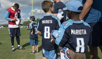 Tennessee Titans quarterback Marcus Mariota (8) signs autographs for kids after the first practice of NFL football training camp, Saturday, July 29, 2017, in Nashville, Tenn. (George Walker IV/The Tennessean via AP)