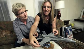 "Alaina Kupec, right, and her wife Kathy Brennan work on putting bombs on a model F18 jet after pulling it out from a moving box in the home they just moved in to, Wednesday, July 26, 2017, in Orange, N.J. Kupec, a transgender woman who worked with pilots who flew F18 jets while serving as a Navy intelligence officer from 1992 until 1995, said she felt ""heartbreak"" after she heard about Trump's Twitter pronouncement banning transgender people from military service.  The 48-year-old publicly transitioned to life as a woman in 2013. (AP Photo/Julio Cortez)"
