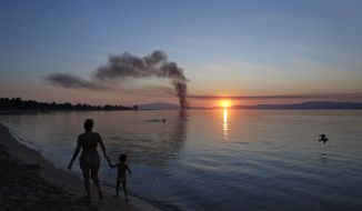 A mother with her child walk at the beach as a smoke from a fire is seen in the background during a sunset at Keramoti in northern Greece, Sunday, July 30, 2017. August is the month when official summer vacations begin for Greeks. (AP Photo/Petros Karadjias)