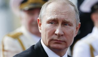 Russian President Vladimir Putin looks on attending the military parade during the Navy Day celebration in St.Petersburg, Russia, on Sunday, July 30, 2017. (AP Photo/Alexander Zemlianichenko, Pool)
