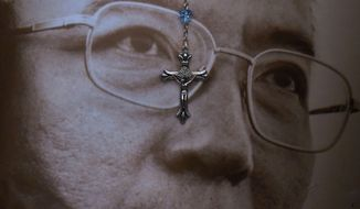 In this Saturday, July 15, 2017 file photo, a rosary hangs over the portrait of the late Chinese Nobel Peace laureate Liu Xiaobo is displayed outside the Chinese liaison office in Hong Kong. China cremated the body of imprisoned Nobel Peace Prize laureate Liu Xiaobo, who died this week after a battle with liver cancer amid international criticism of Beijing for not letting him travel abroad as he had wished. (AP Photo/Vincent Yu, File)
