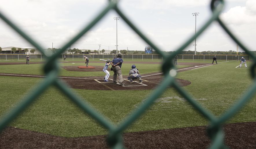 In this Wednesday, June 21, 2017 photo, a game takes place on one of the 15 baseball fields at the Orlando North, Seminole County Sports facility in Sanford, Fla. Most of the fields are covered with synthetic turf and baselines that will drain quickly in case of rain. (AP Photo/John Raoux)