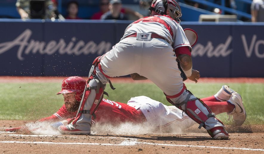 Toronto Blue Jays' Russell Martin is safe at home plate scoring on a sacrifice fly, beating the tag attempt by Los Angeles Angels catcher Martin Maldonado in the third inning of their AL baseball game in Toronto on Sunday, July 30, 2017. (Fred Thornhill/The Canadian Press via AP)