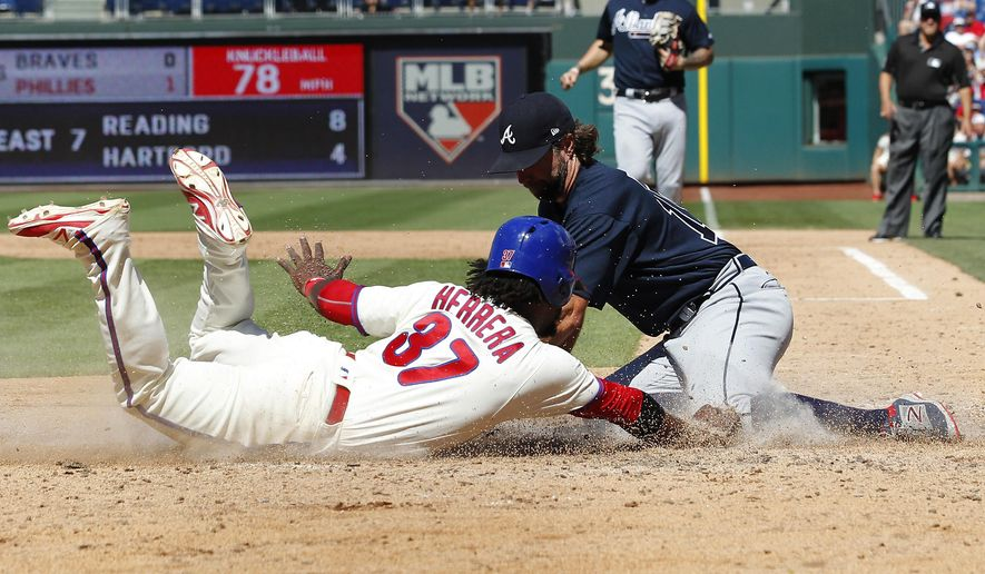Philadelphia Phillies' Odubel Herrera is tagged out at home by Atlanta Braves' pitcher R.A. Dickey after a wild pitch during the sixth inning of a baseball game against the Atlanta Braves, Sunday, July 30, 2017, in Philadelphia. (AP Photo/Tom Mihalek)