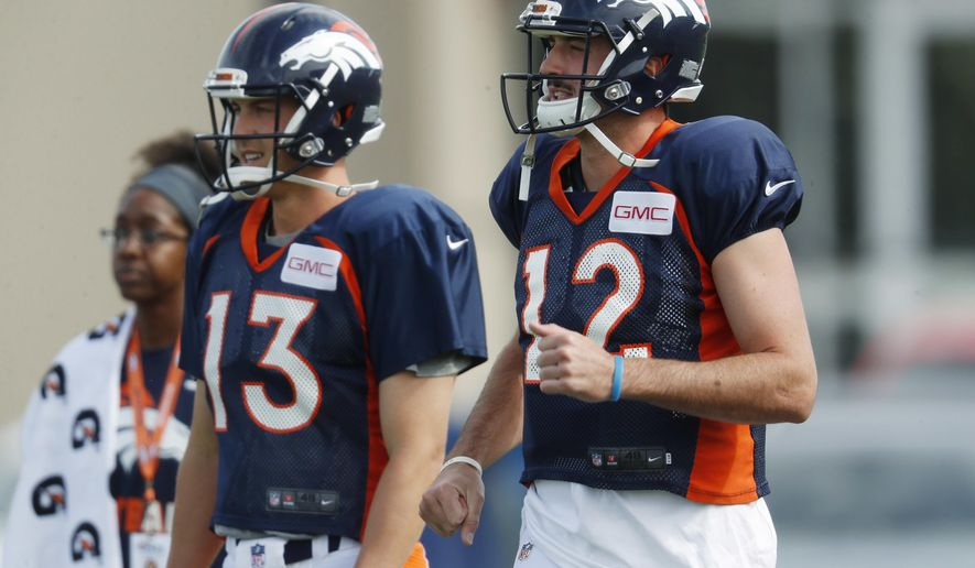 Denver Broncos quarterbacks Paxton Lynch, front, and Trevor Siemian take part in drills at an NFL football training camp Sunday, July 30, 2017, in Englewood, Colo. (AP Photo/David Zalubowski)