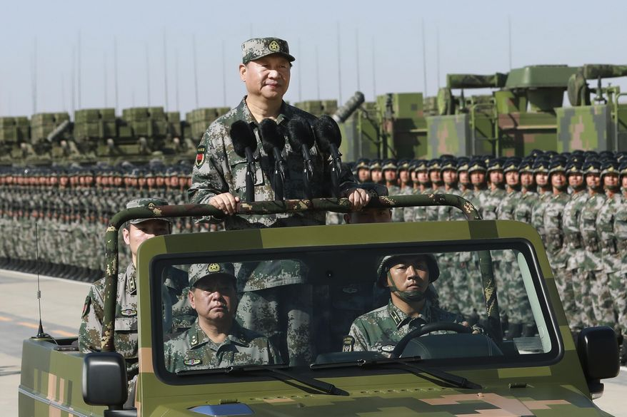 "In this photo released by Xinhua News Agency, Chinese President Xi Jinping stands on a military jeep as he inspects troops of the People's Liberation Army during a military parade to commemorate the 90th anniversary of the founding of the PLA at Zhurihe training base in north China's Inner Mongolia Autonomous Region, Sunday, July 30, 2017. China's military has the ""confidence and capability"" to bolster the country's rise into a world power, President Xi Jinping said Sunday as he oversaw a large-scale military parade meant to show off the forces at his command to foreign and domestic audiences. (Li Gang/Xinhua via AP)"