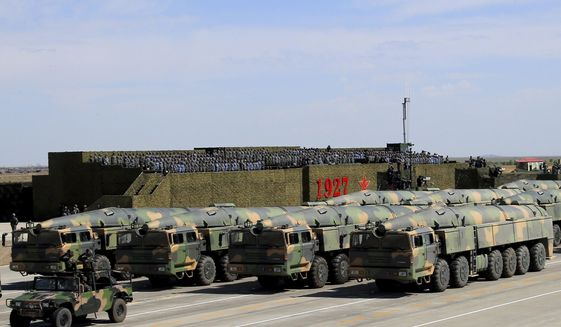"""In this photo released by China's Xinhua News Agency, military vehicles carrying missiles for both nuclear and conventional strikes are driven past the VIP stage during a military parade to commemorate the 90th anniversary of the founding of the People's Liberation Army at Zhurihe training base in north China's Inner Mongolia Autonomous Region, Sunday, July 30, 2017. China's military has the """"confidence and capability"""" to bolster the country's rise into a world power, President Xi Jinping said Sunday as he oversaw a large-scale military parade meant to show off the forces at his command to foreign and domestic audiences. (Zha Chunming/Xinhua via AP)"""