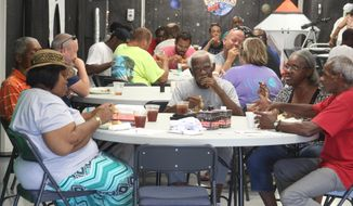 Volunteers take time to eat and pray with patrons at Feeding at 900 Franklin Street. Each week, Myrtha McKinney, left, and other church members come to fellowship with them.  (Anyssa Roberts /The Leaf-Chronicle via AP)
