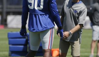 New York Giants' Jason Pierre-Paul, left, talks with defensive coordinator Steve Spagnuolo during NFL football training camp in East Rutherford, N.J., Sunday, July 30, 2017. (AP Photo/Seth Wenig)