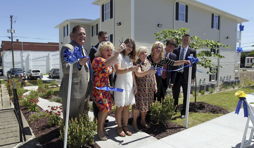 ADVANCE FOR SUNDAY JULY 30 - In this Tuesday, July 25, 2017 photo, a ribbon cutting ceremony is held for the newly constructed Golden Heart Apartments in Kenova, W.Va. The 9,600-square-foot complex at 1205 Chestnut St. in Kenova includes five one-bedroom apartments, five two-bedroom apartments and a 24-hour support staff member apartment. It also has a resource center, providing a space for girls to study and relax together. (Lori Wolfe/The Herald-Dispatch via AP)