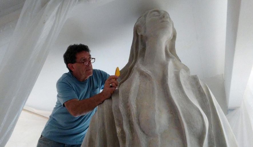 "In this Thursday, July 27, 2017, photo provided by Highstone Studio, sculptor Robert Bruce Epstein uses a hand rasp to contour a sculpture titled ""Lady of the Gulf"" in Lakewood, Colo. The sculpture will be installed this fall in Port Fourchon, La., as a memorial to all those lost at sea in the Gulf of Mexico. Groundbreaking was held Wednesday. Bronzing is among several steps that will be taken before it is shipped from Lakewood, Colorado, to Louisiana. (Leslie Peck-Epstein/Highstone Studio via AP)"