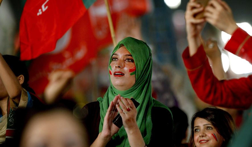 A female supporter of opposition party Pakistan Tehreek-e-Insaf claps while she with others attend a rally in Islamabad, Pakistan, Sunday, July 30, 2017. Thousands of supporters of opposition party Tehreek-e-Insaf rallied in the Pakistani capital Islamabad to celebrate the removal of Prime Minister Nawaz Sharif. (AP Photo/Anjum Naveed)