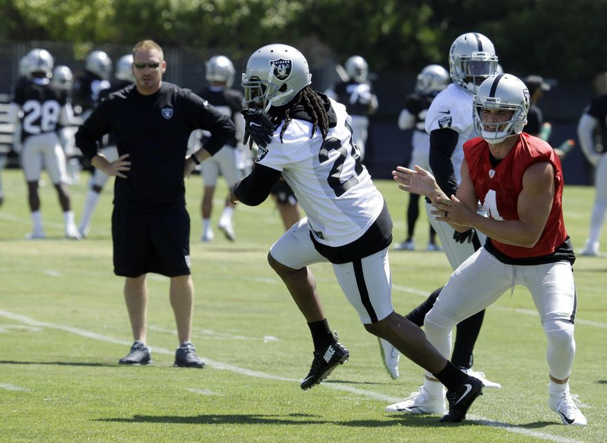 Oakland Raiders quarterback Derek Carr, right, hands the ball off to Marshawn Lynch during an NFL football training camp on Saturday, July 29, 2017, in Napa, Calif. (AP Photo/Ben Margot)
