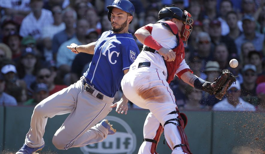Kansas City Royals' Eric Hosmer, left, scores on a hit by Royals' Alcides Escobar as Boston Red Sox's Christian Vazquez, right, tries to get his glove on the ball in the eighth inning of a baseball game, Sunday, July 30, 2017, in Boston. (AP Photo/Steven Senne)