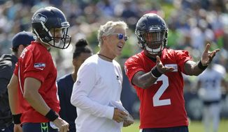 Seattle Seahawks head coach Pete Carroll, center, talks with backup quarterbacks Austin Davis, left, and Trevone Boykin, right, on the first day an NFL football training camp, Sunday, July 30, 2017, in Renton, Wash. (AP Photo/Ted S. Warren) ** FILE **
