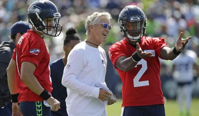 Seattle Seahawks head coach Pete Carroll, center, talks with backup quarterbacks Austin Davis, left, and Trevone Boykin, right, on the first day an NFL football training camp, Sunday, July 30, 2017, in Renton, Wash. (AP Photo/Ted S. Warren)