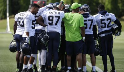 New Seattle Seahawks defensive end Marcus Smith (97) joins in a huddle on the first day an NFL football training camp, Sunday, July 30, 2017, in Renton, Wash. (AP Photo/Ted S. Warren)