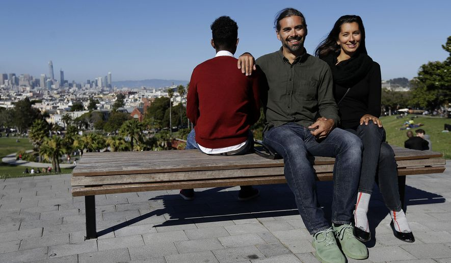 In this July 14, 2017, file photo, Mike Gougherty, center, and Julie Rajagopal, right, pose for photos with their 16-year-old foster child from Eritrea at Dolores Park in San Francisco. When their 16-year-old foster child landed in March, he was among the last refugee foster children to make it into the U.S. Trump administration travel bans declared to block terrorists also are halting a small, three-decade-old program bringing orphan refugee children to waiting foster families in the United States. (AP Photo/Jeff Chiu)
