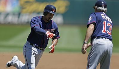 Minnesota Twins' Eduardo Escobar, left, is congratulated by third base coach Gene Glynn (13) after hitting a two-run home run off Oakland Athletics' Jharel Cotton in the first inning of a baseball game Sunday, July 30, 2017, in Oakland, Calif. (AP Photo/Ben Margot)