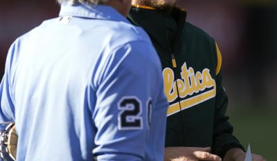 Oakland Athletics' Sonny Gray, right, talks with home plate umpire Tom Hellion before  a baseball game against the Minnesota Twins, Saturday, July 29, 2017, in Oakland, Calif. (AP Photo/D. Ross Cameron)