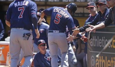 Minnesota Twins' Eduardo Escobar (5) is congratulated after hitting a two run home run off Oakland Athletics' Jharel Cotton in the first inning of a baseball game Sunday, July 30, 2017, in Oakland, Calif. (AP Photo/Ben Margot)