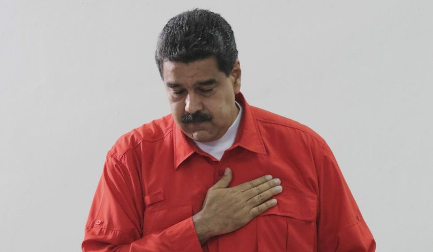 In this photo released by Miraflores Press Office, Venezuela's President Nicolas Maduro gestures after he casts his ballot as he votes for a constitutional assembly in Caracas, Venezuela on Sunday, July 30, 2017. (Miraflores Press Office via AP)