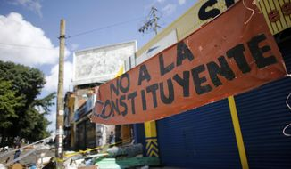 """A banner that reads in Spanish """"No to the Constituent Assembly"""" seen at Petare neighborhood in Caracas, Venezuela, Saturday, July 29, 2017. Despite four months of deadly protests and the threat of U.S. sanctions, Venezuela on Saturday found itself 24 hours away from a consolidation of government power that appeared certain to drag the OPEC nation deeper into a crisis that has entire neighborhoods battling police and paramilitaries while the poor root for scraps in piles of trash. (AP Photo/Ariana Cubillos)"""