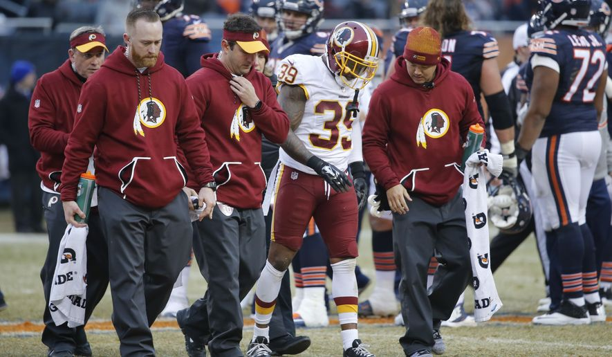 Washington Redskins running back Keith Marshall (39) walks off the field with trainers against the Chicago Bears during the second half of an NFL football game, Saturday, Dec. 24, 2016, in Chicago. (AP Photo/Charles Rex Arbogast)