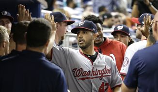 Washington Nationals starting pitcher Gio Gonzalez is high-fived in the dugout after being relieved during the ninth inning of a baseball game against the Miami Marlins, Monday, July 31, 2017, in Miami. The Nationals won 1-0. Gonzalez gave up a single to Miami Marlins second baseman Dee Gordon in the ninth inning to end his bid for a no-hitter. (AP Photo/Lynne Sladky)