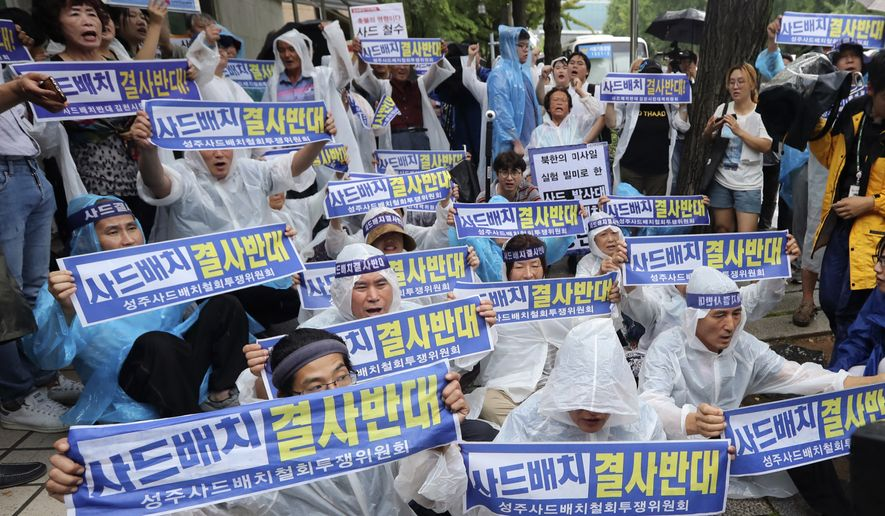 "South Korean protesters and residents attend a rally against the deployment of an advanced U.S. missile defense system called Terminal High-Altitude Area Defense, or THAAD, near the presidential Blue House in Seoul, South Korea, Monday, July 31, 2017. They gathered to oppose the government's plan to install additional THAAD launchers. Banners held by the protesters read: ""Absolutely oppose to THAAD deployment."" (AP Photo/Lee Jin-man)"