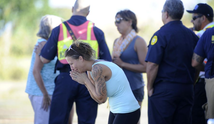 In this Saturday, July 29, 2017, photo, friends or relatives of the victims of the small plane crash react to the news of the fate of the passengers of the plane at an Honolulu Fire Department helicopter staging area in Kunia, Hawaii. Federal investigators haven't yet determined what caused the plane to crash in an inaccessible mountainous area on the island of Oahu. Hutton and his three passengers died in the crash. (Bruce Asato/The Star-Advertiser via AP)