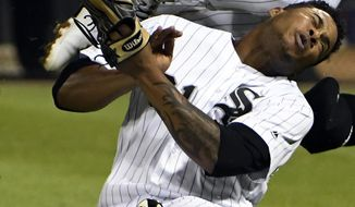 Chicago White Sox second baseman Yoan Moncada, top, and Chicago White Sox right fielder Willy Garcia, bottom, collide on a double hit by Toronto Blue Jays' Darwin Barney during the sixth inning of a baseball game, Monday, July 31, 2017, in Chicago. Both players had to leave the game. (AP Photo/David Banks)