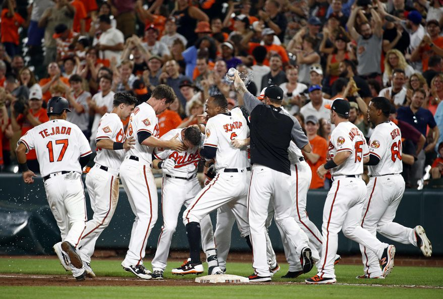 Members of the Baltimore Orioles celebrate with Craig Gentry, fourth from left, after he drove in the game-winning run on a single in the ninth inning of a baseball game against the Kansas City Royals in Baltimore, Monday, July 31, 2017. Baltimore won 2-1. (AP Photo/Patrick Semansky)