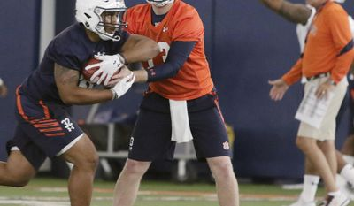 Auburn quarterback Sean White hands off to running back Malik Miller in NCAA college football practice on Monday, July 31, 2017, in Auburn, Ala. (Todd J. Van Emst/Opelika-Auburn News via AP)