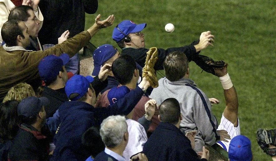 FILE - In this Oct 14, 2003, file photo, Steve Bartman, top center, catches a ball as Chicago Cubs left fielder Moises Alou's arm is seen reaching into the stands, at right, against the Florida Marlins in the eighth inning during Game 6 of the National League championship series Tuesday, Oct. 14, 2003, at Wrigley Field in Chicago. The Cubs announced Monday, July 31, 2017, they were giving a 2016 World Series championship ring to Bartman, the fan remembered for deflecting a foul ball that appeared destined to land in left fielder Moises Alou's glove with Chicago five outs from the World Series in 2003. (AP Photo/Morry Gash, File)