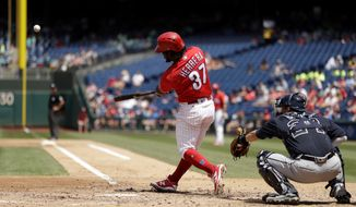 Philadelphia Phillies' Odubel Herrera follows through on a three-run home run off Atlanta Braves starting pitcher Mike Foltynewicz during the third inning of a baseball game, Monday, July 31, 2017, in Philadelphia. At right is Braves catcher Kurt Suzuki. (AP Photo/Matt Slocum)