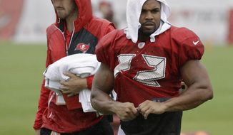 Tampa Bay Buccaneers running back Doug Martin (22) is covered up as rain associated with Tropical Storm Emily falls during an NFL football training camp practice Monday, July 31, 2017, in Tampa, Fla. (AP Photo/Chris O'Meara)