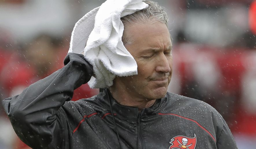 Tampa Bay Buccaneers head coach Dirk Koetter towels off as rains associated with Tropical Storm Emily falls during an NFL football training camp practice Monday, July 31, 2017, in Tampa, Fla. (AP Photo/Chris O'Meara)