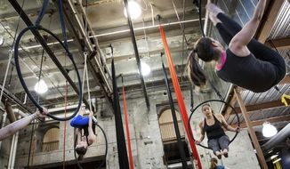 Jenly Deiter, left, co-owner of Iron City Circus Arts, demonstrates a move on an aerial hoop for Djuna Gulliver, Lawrenceville, center, and Justine Vanella, Brookline, right, during a class on Tuesday, June 27, 2017 in South Side. People come from neighborhoods all over Pittsburgh to attend class. (Alex Driehaus/Pittsburgh Post-Gazette via AP)
