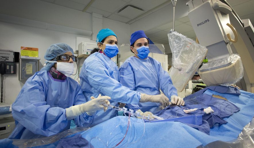 In this Feb. 16, 2017 photo, Dr. Annapoorna Kini, center, performs a non-emergency angioplasty at Mount Sinai Hospital in New York. Through a blood vessel in the groin, she guides a tube to a blockage in the heart. She inflates a tiny balloon to flatten the clog, and leaves behind a mesh tube called a stent to prop the artery open. (AP Photo/Mark Lennihan)
