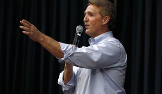 "FILE- In this April 13, 2017, file photo, Arizona Republican Sen. Jeff Flake takes a question from the audience during a town hall in Mesa, Ariz. The debut of Flake's book ""Conscience of a Conservative"" goes on sale on Tuesday, Aug. 1. (AP Photo/Ross D. Franklin, File)"