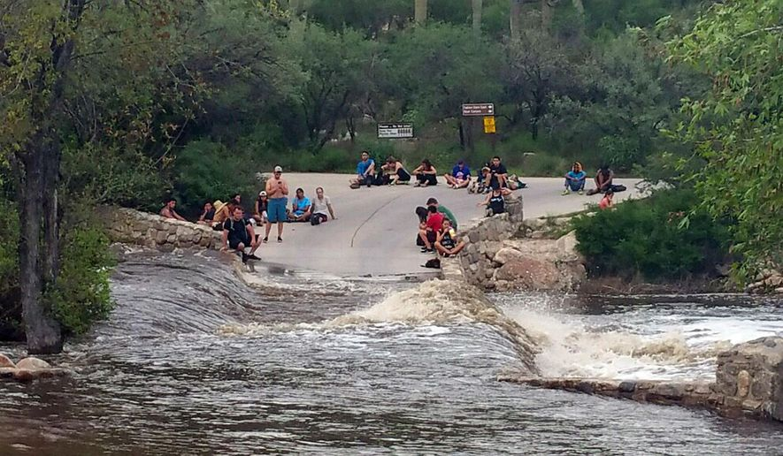 This photo provided by the Pima County Sheriff's office shows hikers stranded by flash flooding in the Sabino Canyon Recreation Park in the outskirts of Tucson, Ariz., Sunday, July 30, 2017. A police helicopter rescued approximately 35 hikers stranded by the flooding a week after 17 people rescued after flash flooding through a different canyon several miles away and 15 days after 10 people died in flash flooding elsewhere in Arizona. (Pima County Sheriff's Office via AP)
