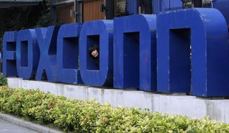 In this May 27, 2010, file photo, a worker looks out through the logo at the entrance of the Foxconn complex in the southern Chinese city of Shenzhen. Conservationists are lining up to oppose Republican plans to eliminate key environmental regulations as part of an incentive package to lure a $10 billion Foxconn electronics plant to southeastern Wisconsin. Gov. Scott Walker's incentives bill would exempt the company from environmental impact statements and state permits for filling wetlands and building on lake beds. (AP Photo/Kin Cheung, File)